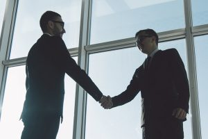 two cyber security experts shaking hands