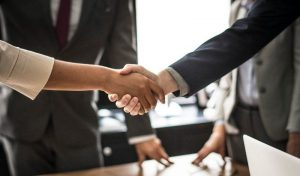 two people shaking hands after forming a partnership